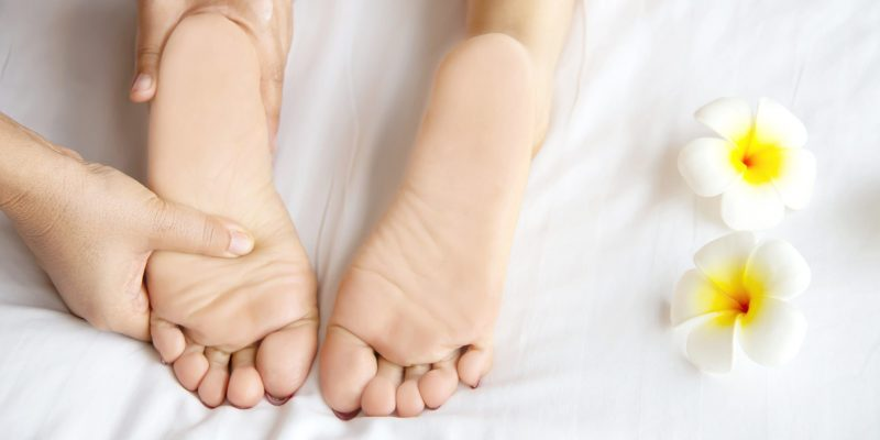 Woman receiving foot massage service from masseuse close up at hand and foot - relax in foot massage therapy service concept
